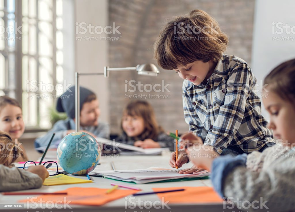 Smiling creative little boy sketching. stock photo