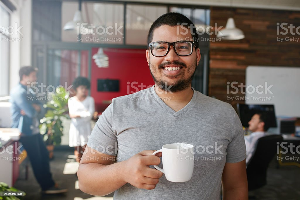 Smiling creative professional having coffee in office stock photo