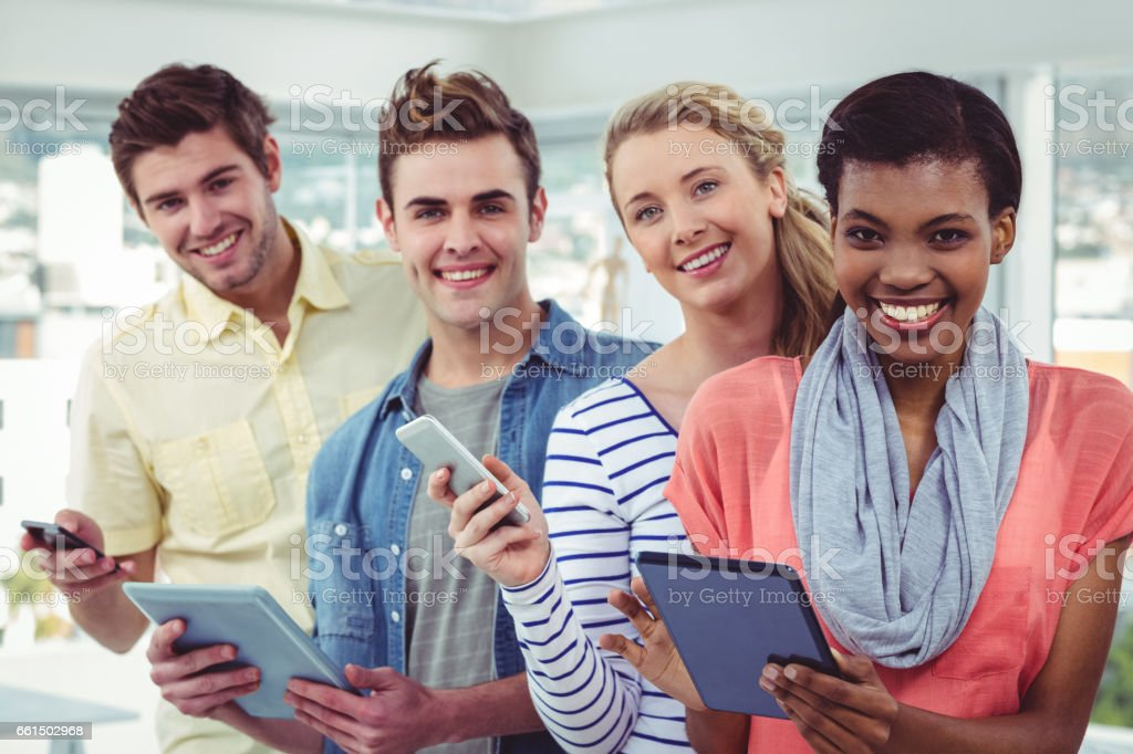 Smiling creative team standing in a line using technology royalty-free stock photo
