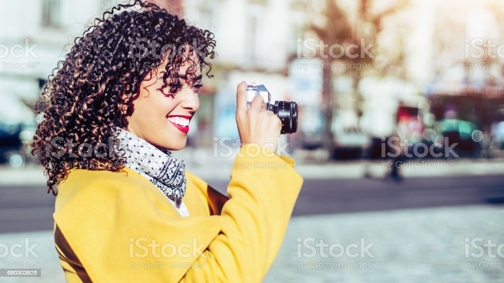 Smiling curly Brazilian girl with retro photo camera stock photo