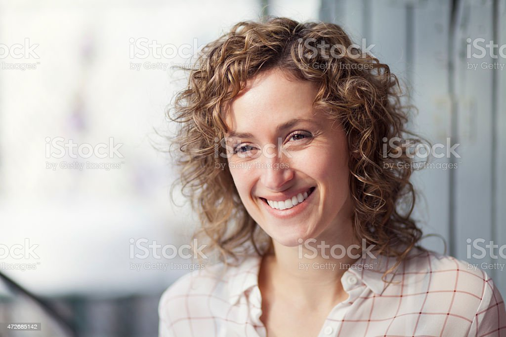 Smiling, curly haired woman's head shot stock photo
