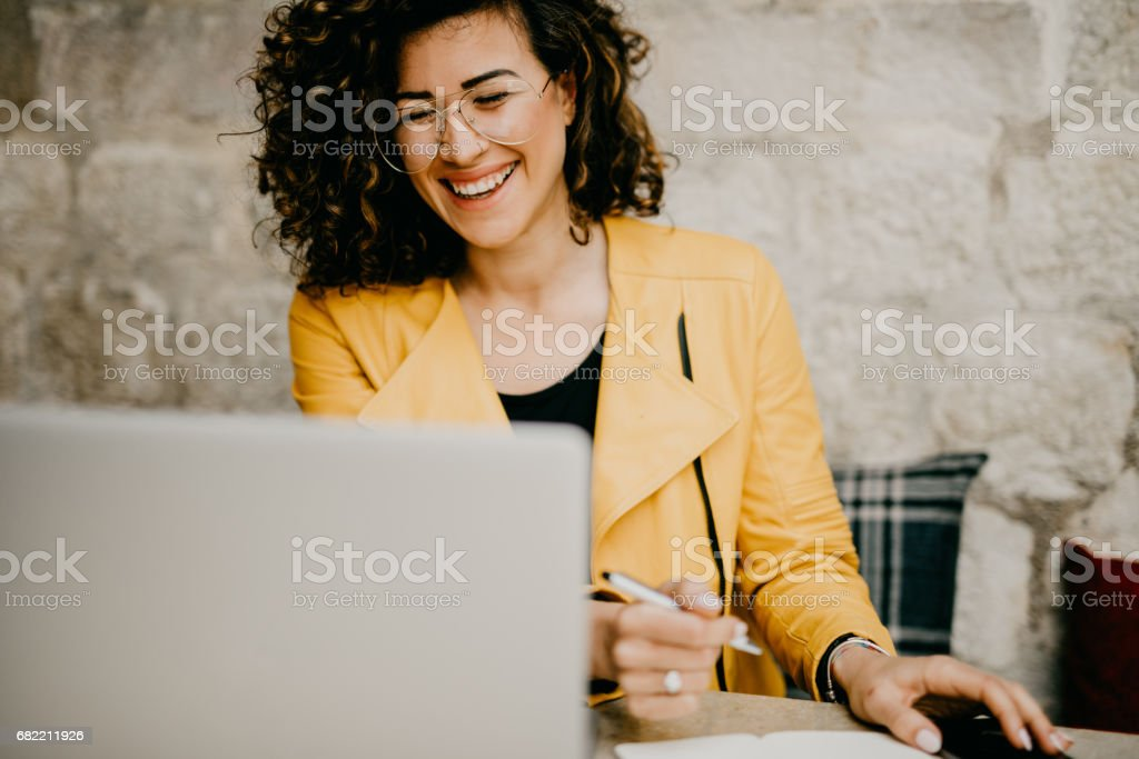 Smiling curly-haired woman is writing down details from laptop stock photo