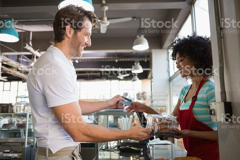 Smiling customer paying by credit card stock photo