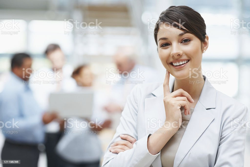 Smiling cute business woman with colleagues at the back royalty-free stock photo