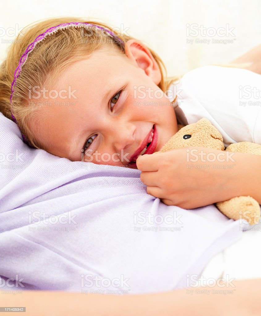 Smiling cute girl lying on her mother's stomach stock photo