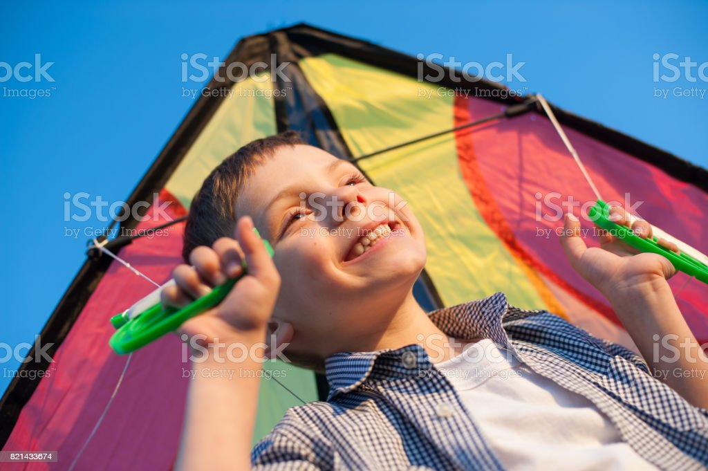 smiling cute little child with colorful kite behind his shoulders stock photo