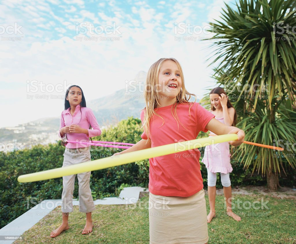 Smiling cute little girls playing with the hula hoop stock photo