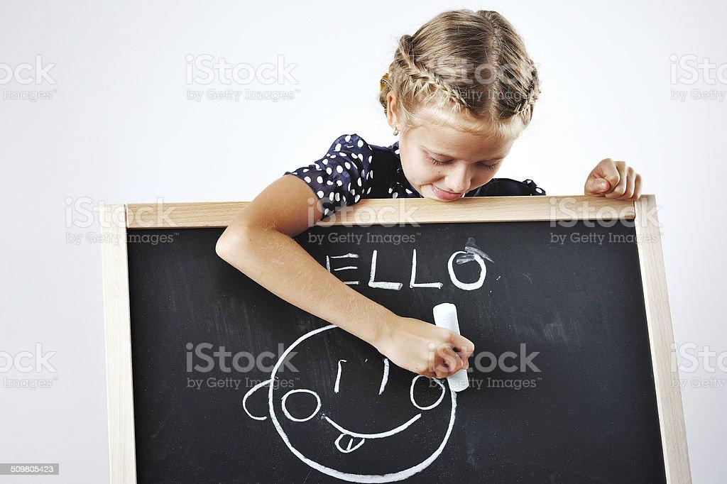 Smiling cute school girl drawing stock photo