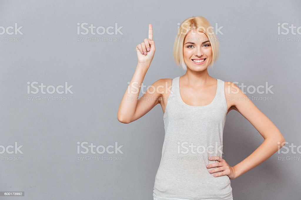 Smiling cute young woman pointing up stock photo
