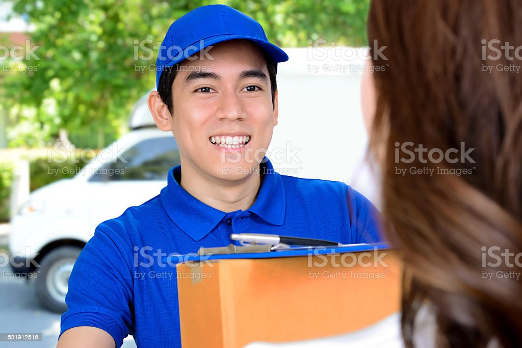 Smiling delivery man delivering a package stock photo