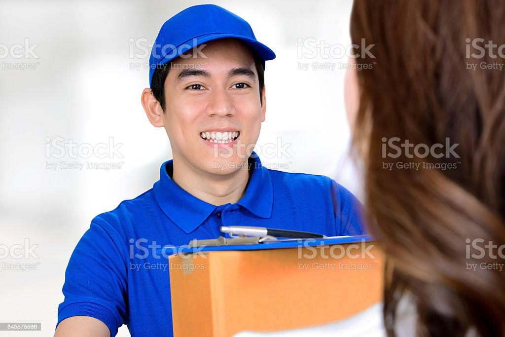 Smiling delivery man delivering a package to a woman stock photo