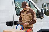 Smiling Delivery Man Holding Digital Tablet Against Truck
