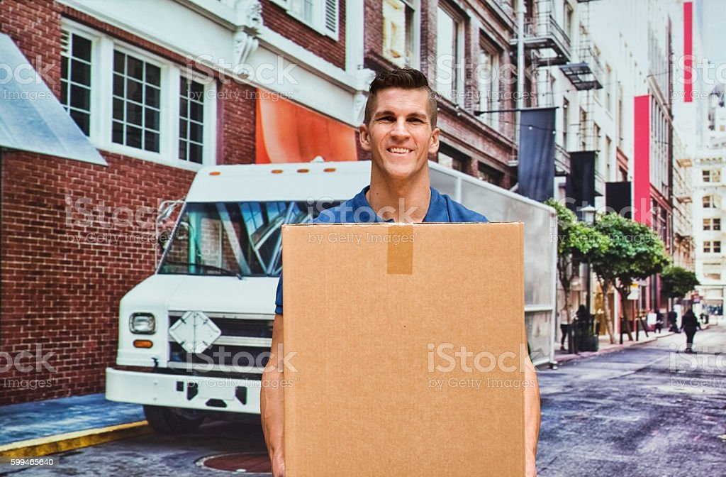 Smiling delivery person carrying box stock photo