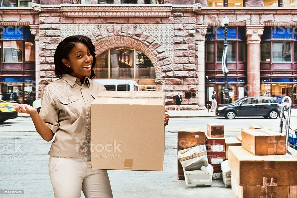 Smiling delivery person presenting outdoors stock photo