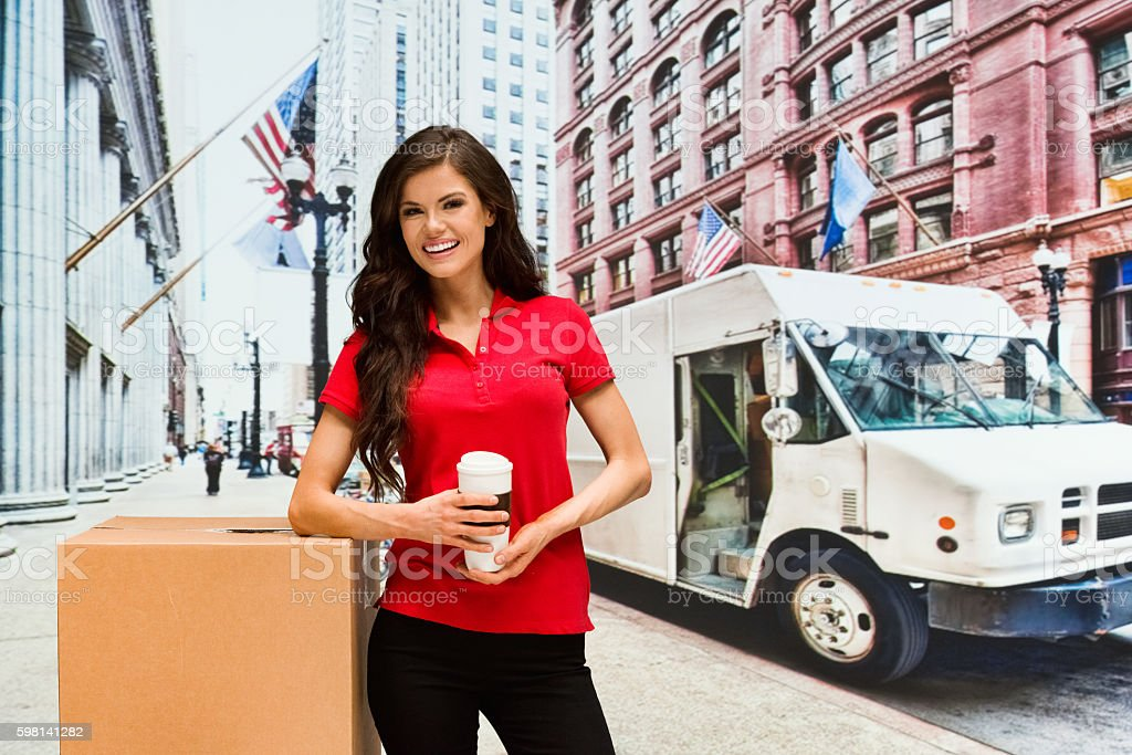 Smiling delivery person standing outdoors stock photo