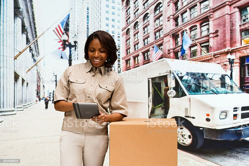 Smiling delivery person using tablet outdoors stock photo