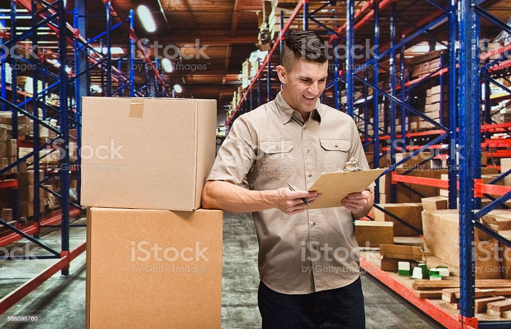 Smiling delivery person working in warehouse stock photo