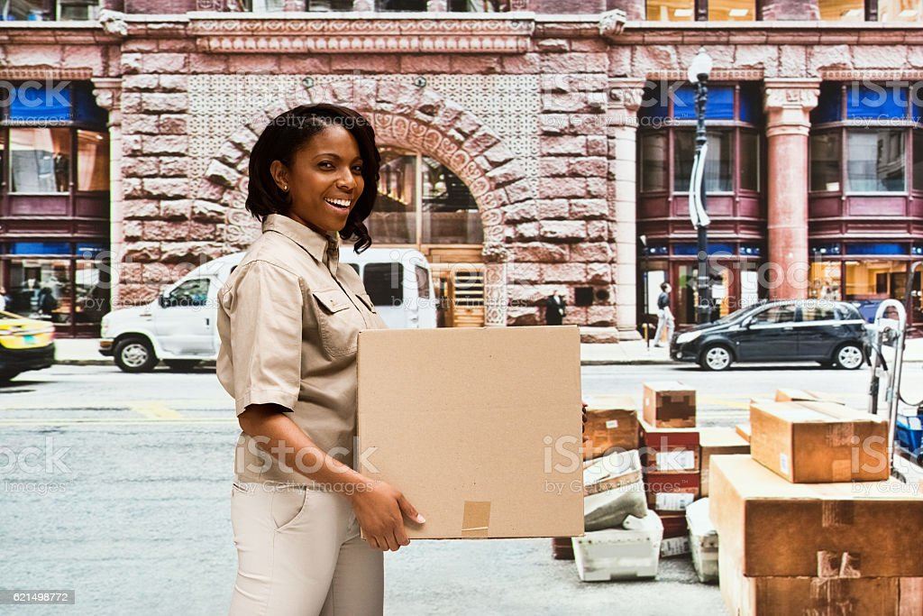 Smiling delivery worker holding box outdoors stock photo