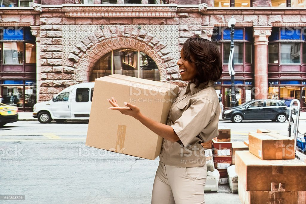 Smiling delivery worker presenting outdoors stock photo