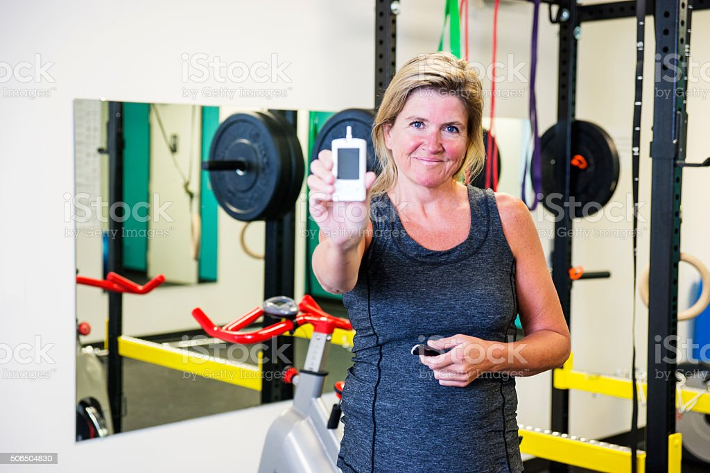 Smiling diabetic woman checking her blood sugar in the gym stock photo