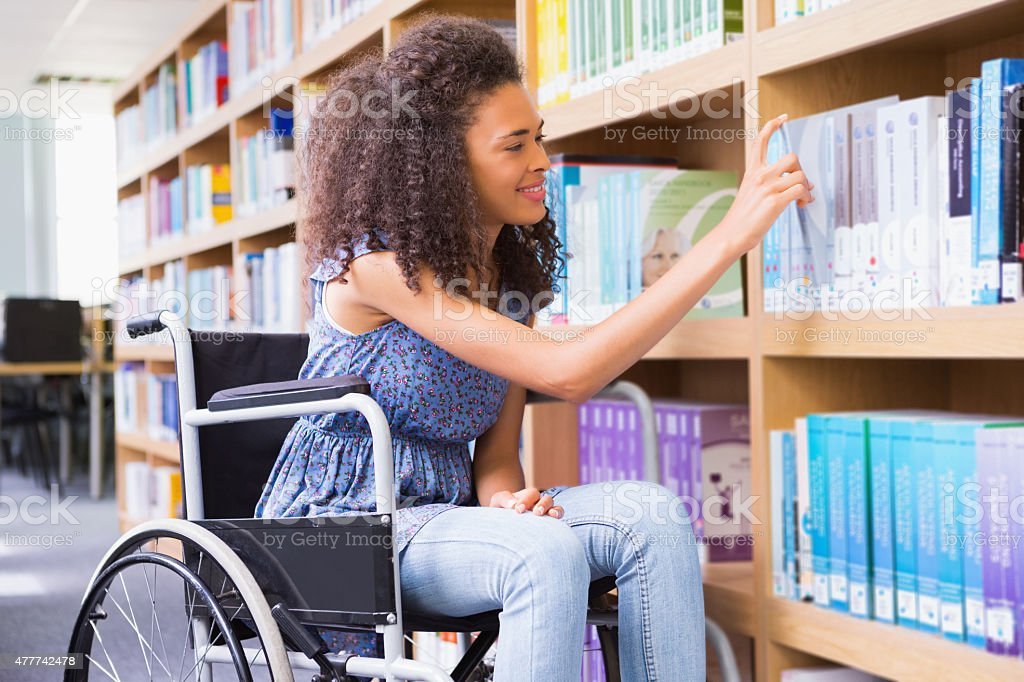 Smiling disabled student in library picking book stock photo