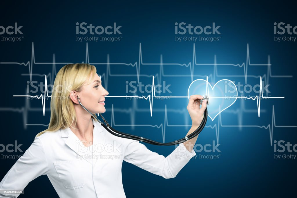 Smiling doctor checking heartbeat stock photo