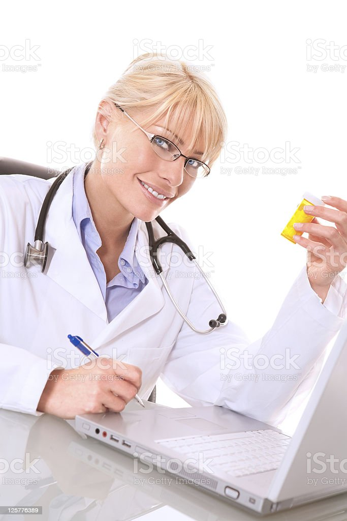 Smiling doctor holding bottle of pills royalty-free stock photo