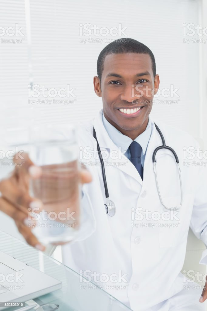 Smiling doctor holding out a glass of water in medical office stock photo