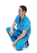 Smiling doctor kneeling and looking away
