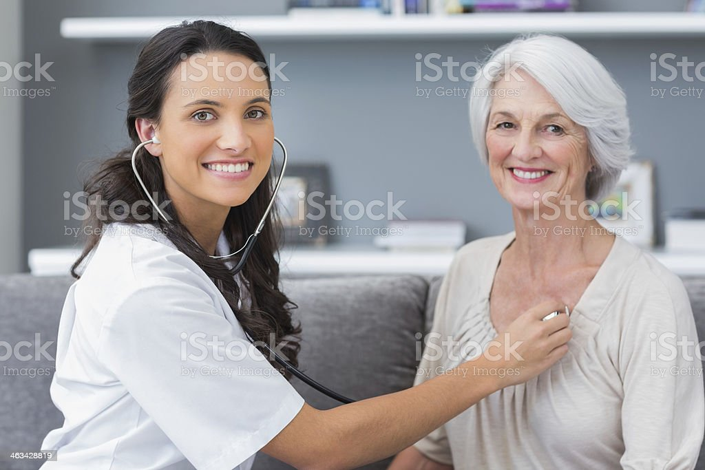 Smiling doctor listening to heart of her patient stock photo