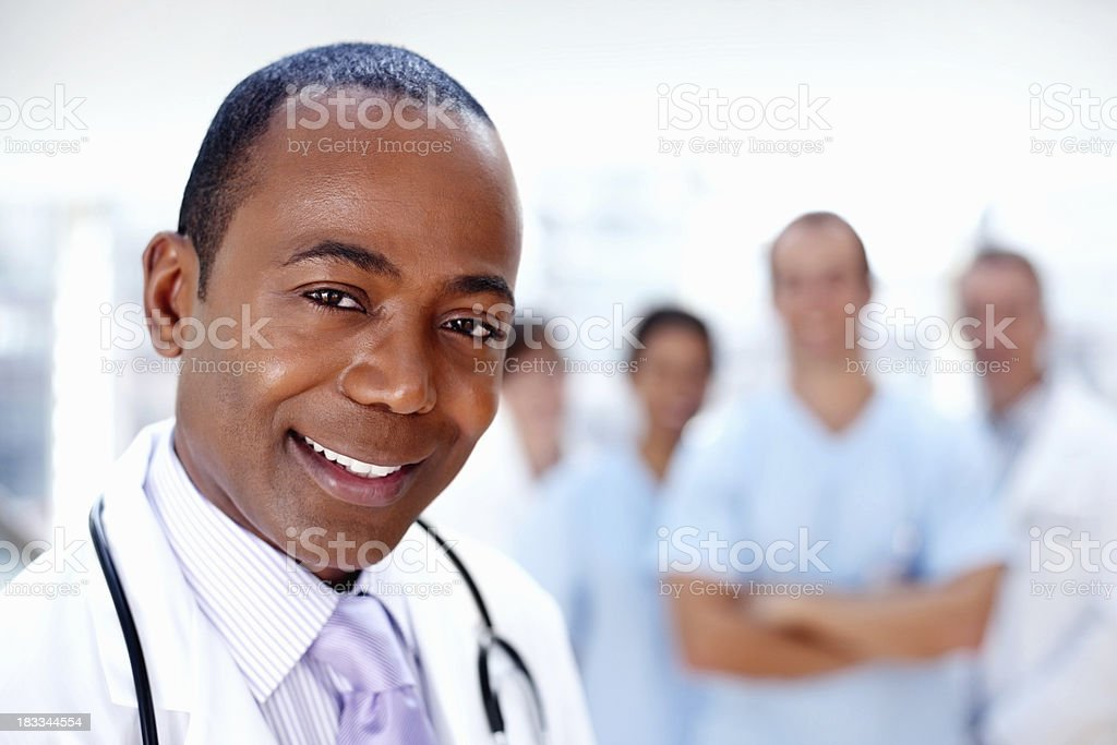 Smiling doctor supported by medical team in background royalty-free stock photo