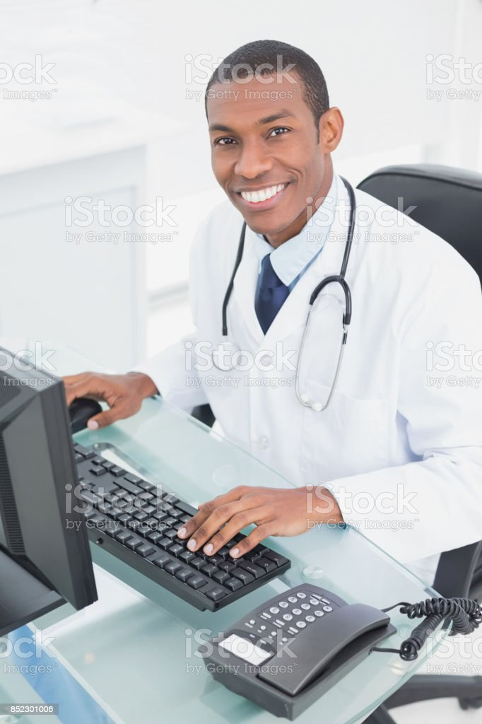 Smiling doctor using computer at medical office stock photo