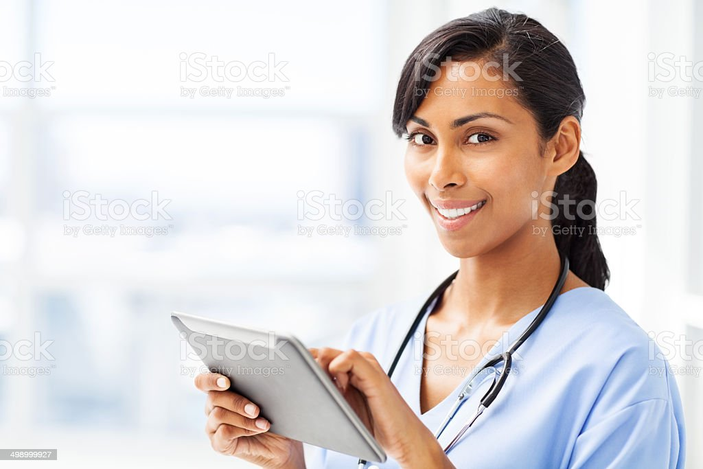 Smiling Doctor Using Digital Tablet In Hospital stock photo
