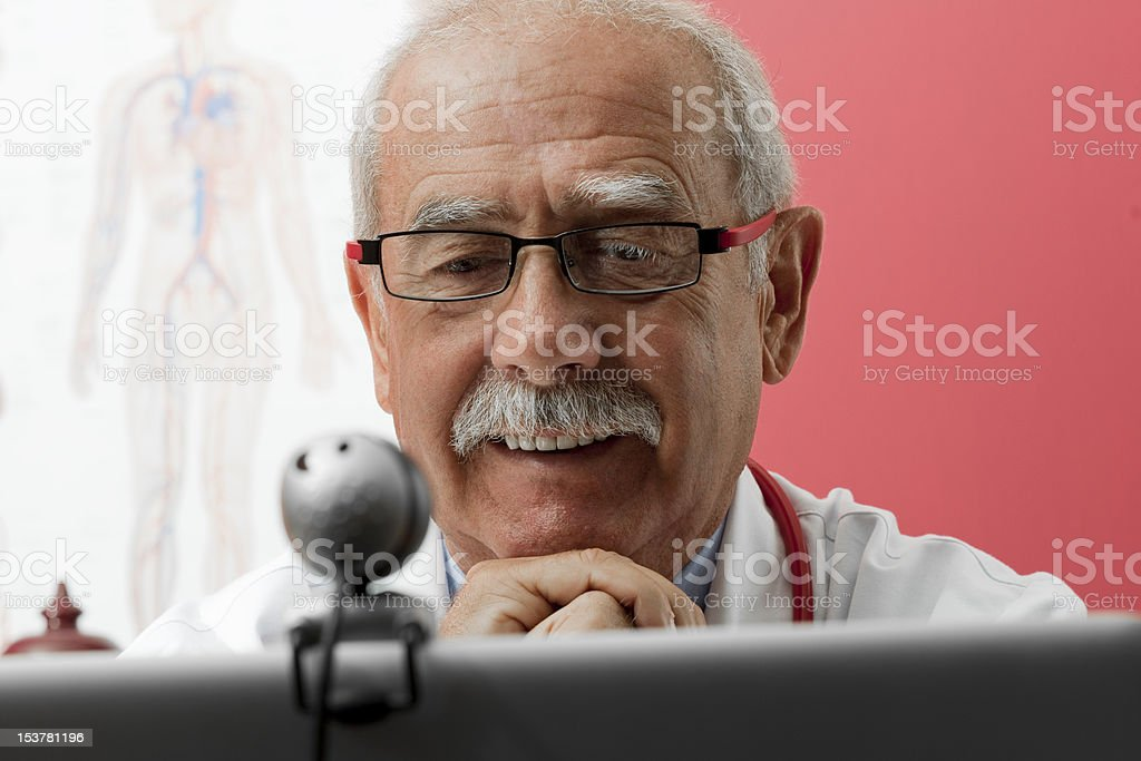 Smiling Doctor Using Webcam stock photo