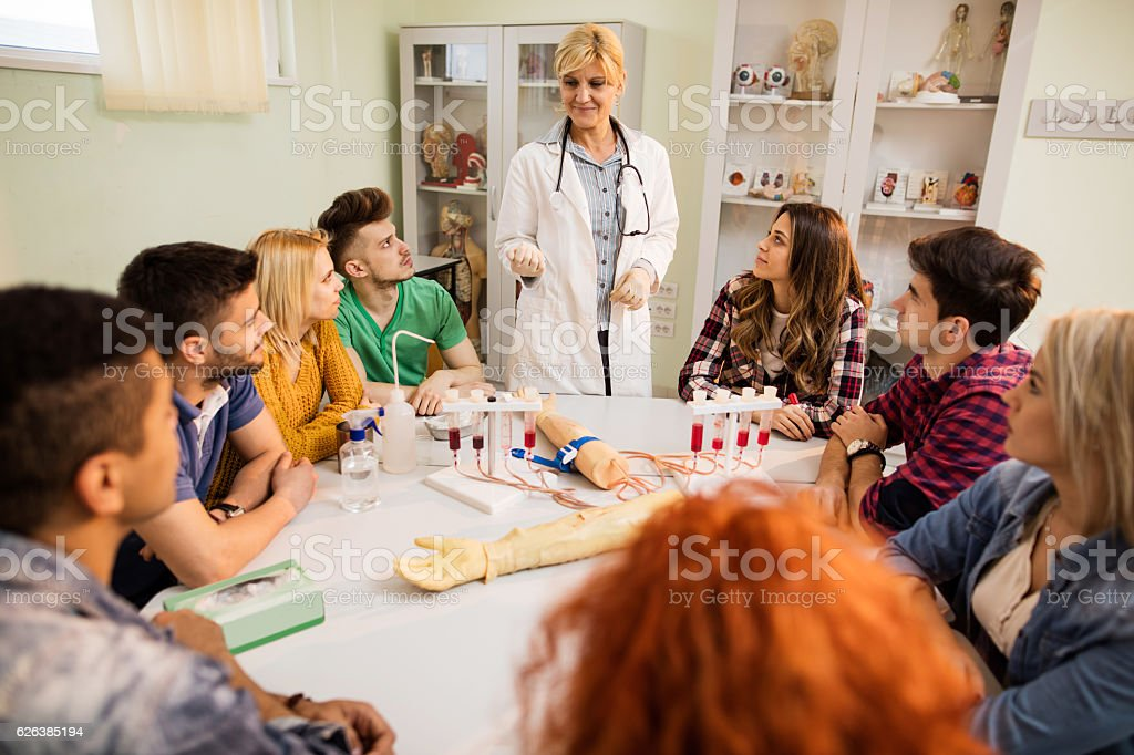 Smiling doctor with medical students during lecture in the laboratory. stock photo