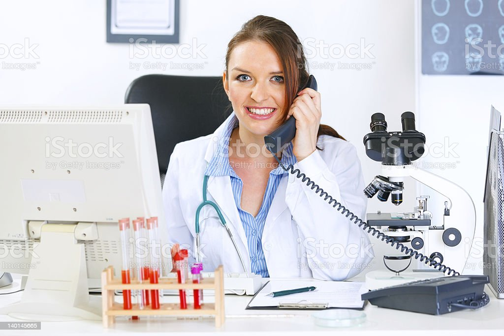 Smiling doctor woman sitting at table and talking on phone royalty-free stock photo
