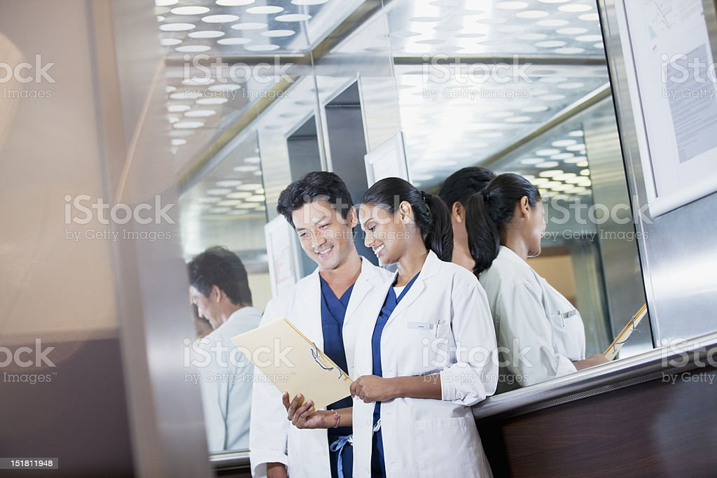 Smiling doctors reviewing medical record in hospital elevator royalty-free stock photo