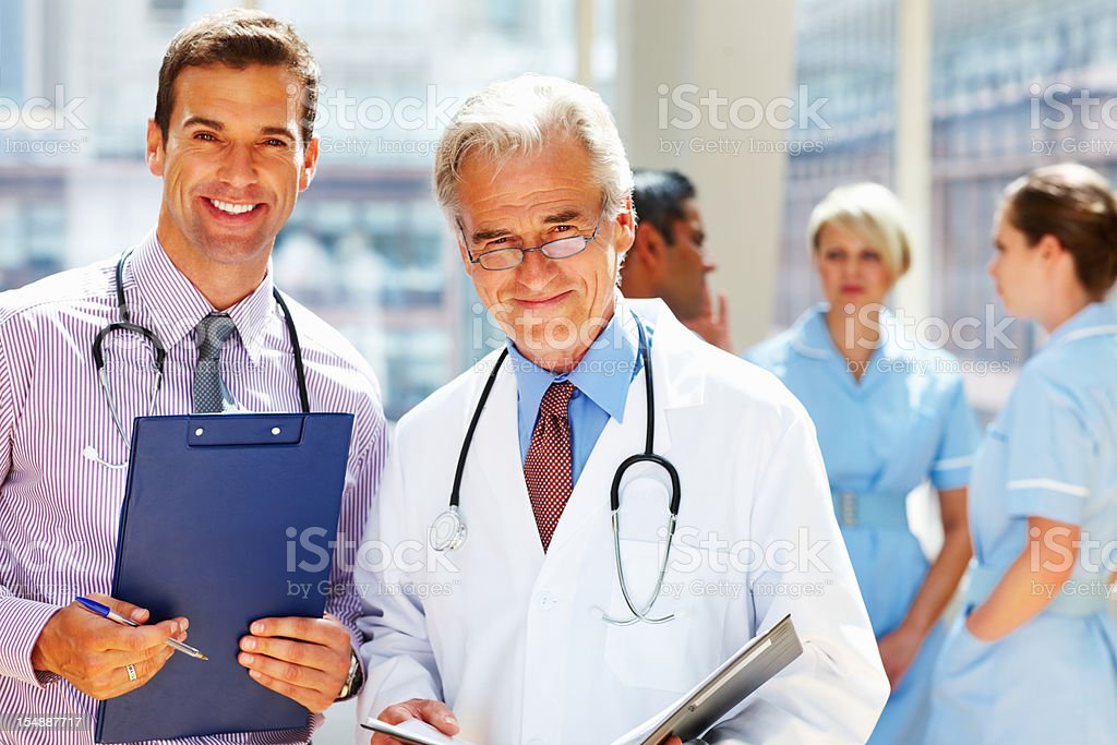 Smiling doctors supported by their staff royalty-free stock photo