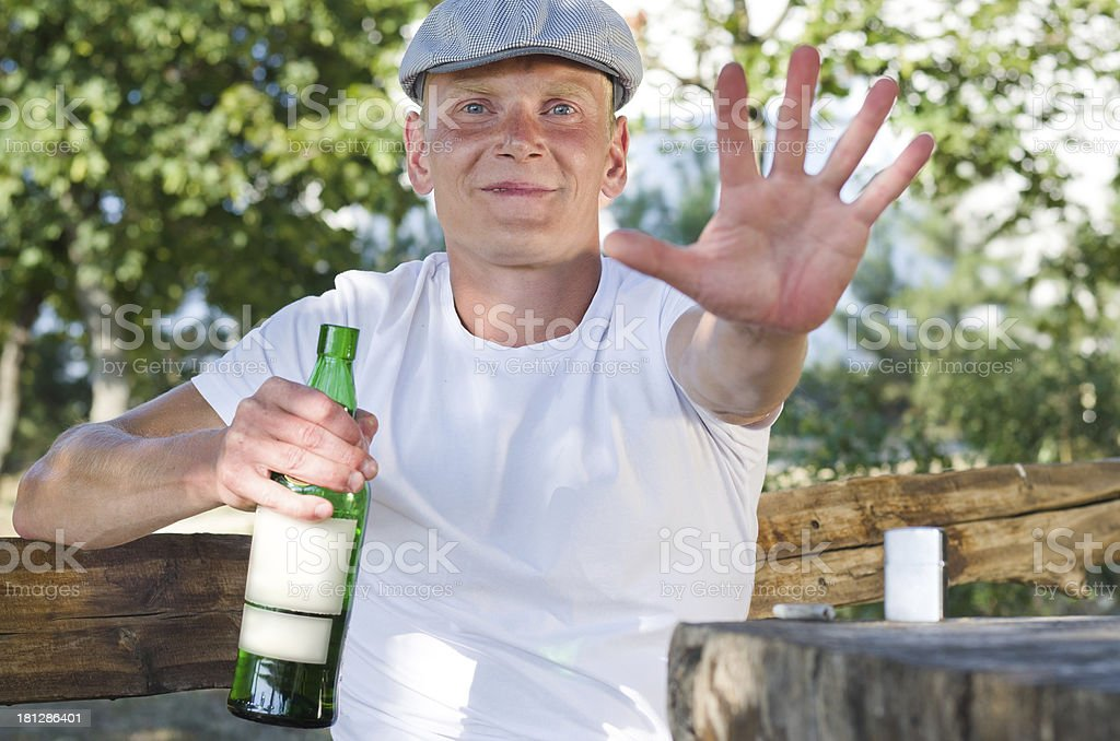 Smiling drunk defending his bottle of alcohol stock photo