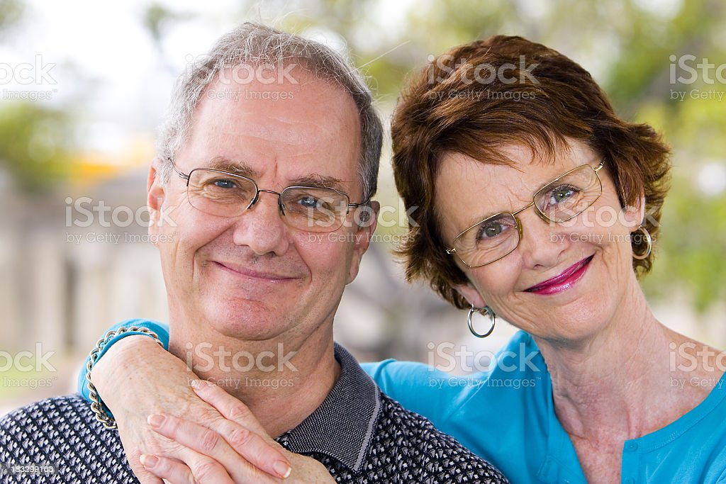 A smiling, elderly couple standing outdoors royalty-free stock photo