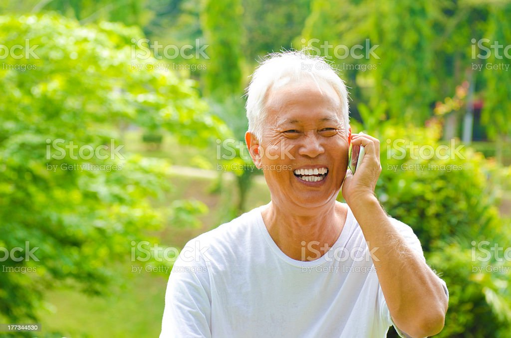 A smiling, elderly man talking on the phone royalty-free stock photo