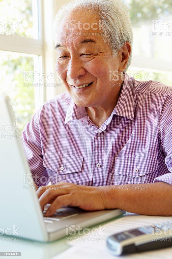 Smiling elderly Taiwanese man On laptop royalty-free stock photo