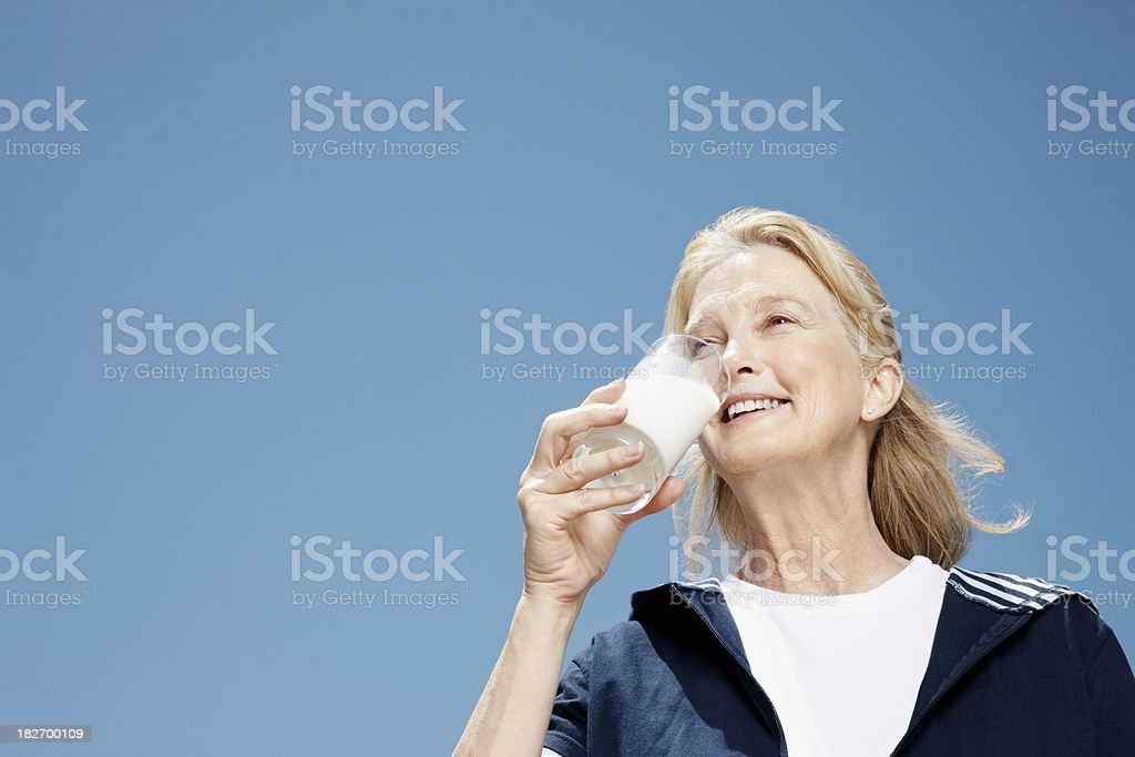 Smiling elderly woman drinking glass of milk royalty-free stock photo