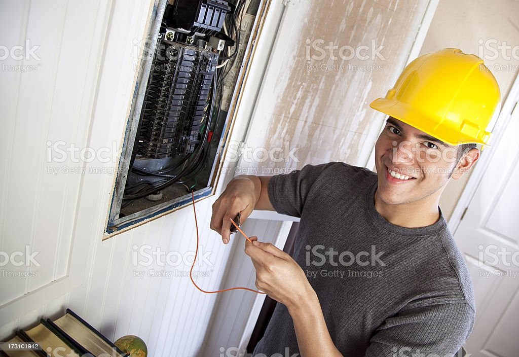 Smiling electrician working on circuit breaker box stock photo