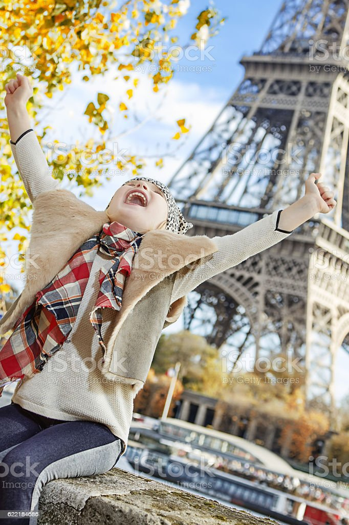 smiling elegant child on embankment in Paris, France rejoicing stock photo