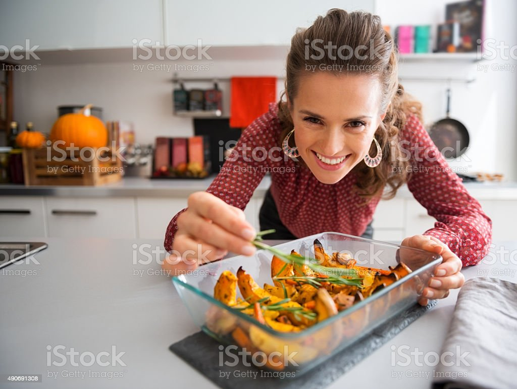 Smiling elegant woman preparing roasted pumpkin dish stock photo