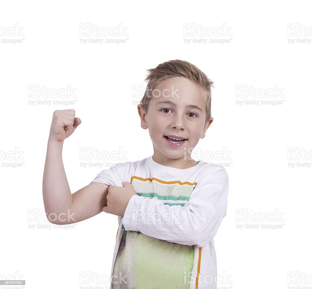 Smiling elementary boy flexing biceps stock photo