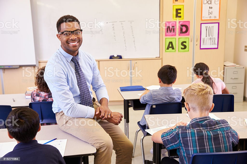 Smiling elementary school teacher sitting on a pupil's desk stock photo