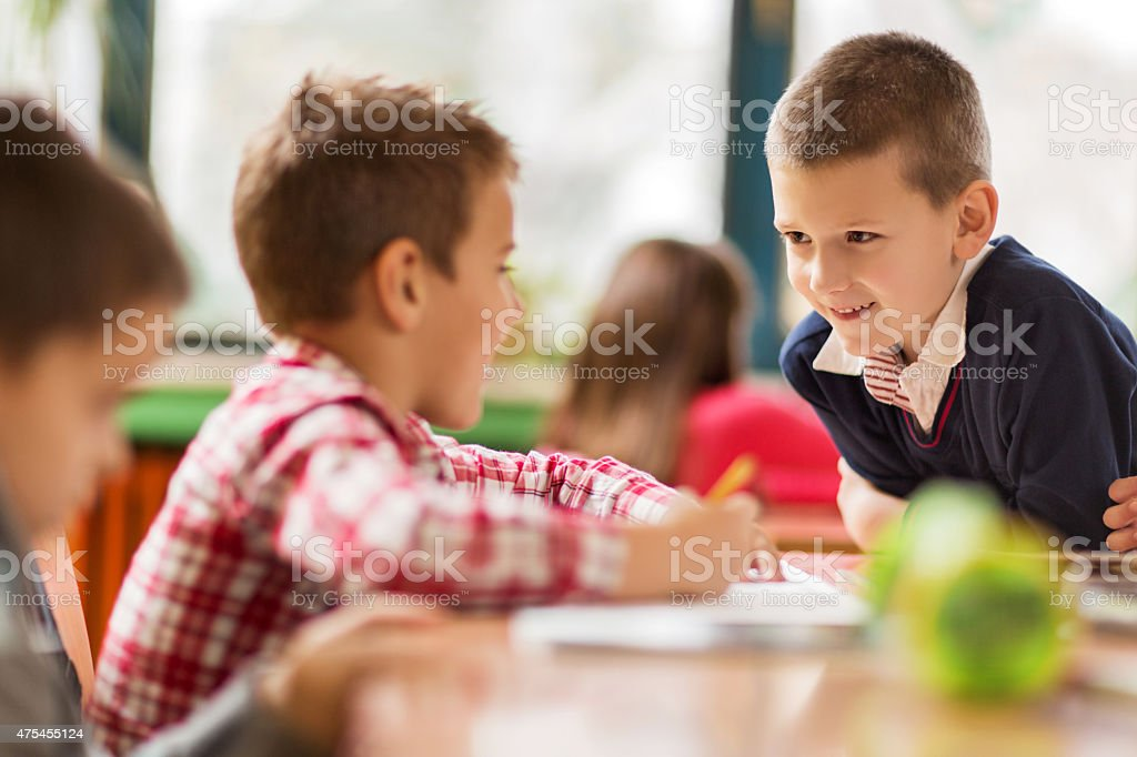 Smiling elementary student talking to his friend in the classroom. stock photo