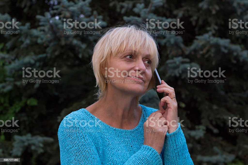 Smiling ellderly woman has a conversation by phone stock photo